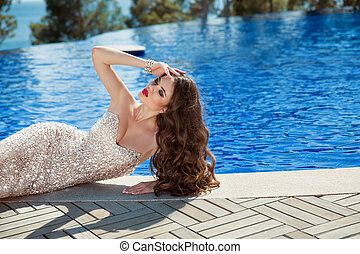 Elegant sexy woman in fashion dress lying by blue swimming...