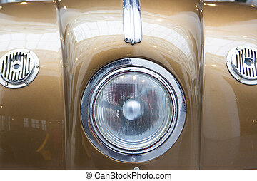 Central headlight detail on a goldenrod classic car. Closeup
