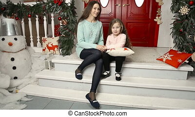Mom and daughter sit near the door