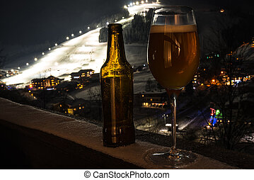 Glass and bottle with craft beer on a balcony at skiing village