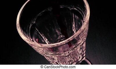 Slow mo pouring red wine in glass faceted - Slow mo pouring...