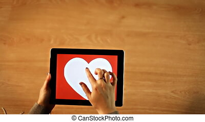 Female drawing heart insight heart on tablet