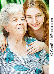 Happy family portrait - daughter and grandmother outdoor