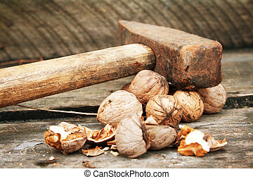 Walnuts and old vintage hammer on wooden table