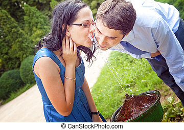 Happy romantic couple drinking water from park fountain -...