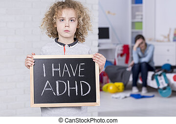 "Boy holding blackboard with ""i have ADHD"" text"