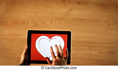 Female drawing heart insight two heart on tablet hd