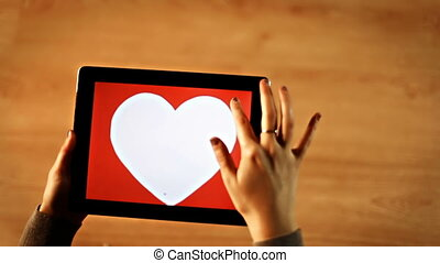 Female drawing heart with arrow on tablet