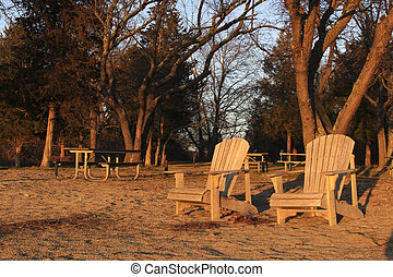wooden chairs on beach at sunset