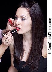 Make-up artist applying gloss on lips - Make-up artist...