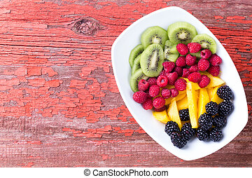 Plate of various fruit in plate on corner of table - Single...