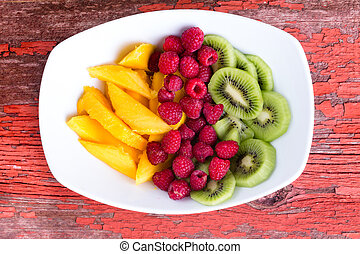 Colorful and delicious fruit in plate on table - Mango and...