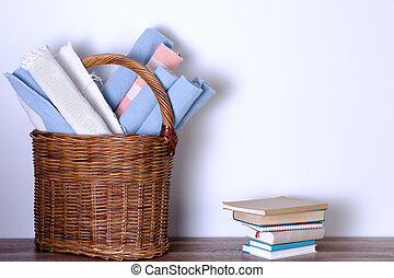 Rugs in Basket and Piled Books Against White Wall