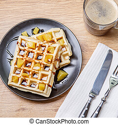 Black plate with homemade waffles, tangerines, chocolate and...
