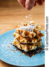 Man sprinkles homemade waffles coconut. Cooking background.