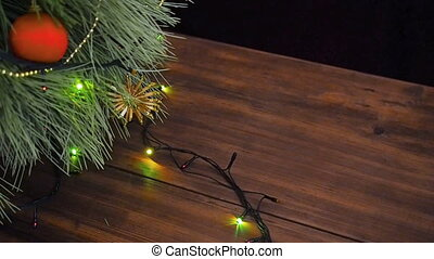 The man puts gift boxes under the Christmas tree. Fir stand...