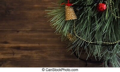 The man puts gift boxes under the Christmas tree. Fir stand on the wooden table and decorated with glowing garland and Christmas toys.