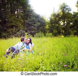 Kiss of romantic lovers in the green grass