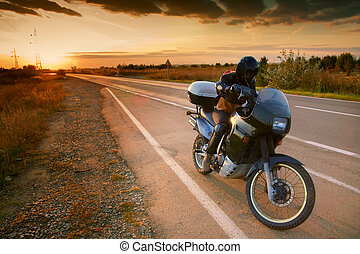 Biker and motorcycle on road at sunset - Biker and...