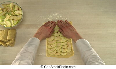 Putting sliced apples on kneaded dough. - Cook putting...