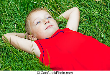 Pensive child day dreaming in fresh grass