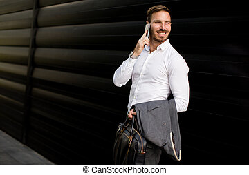 Young businessman outdoor and talking over the mobile phone