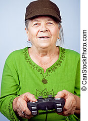 Happy senior woman playing video games with gamepad