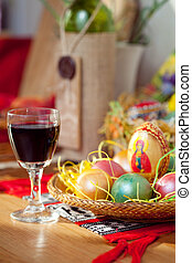 Easter painted eggs and wine glass on table