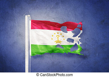 Torn flag of Tajikistan flying against grunge background.