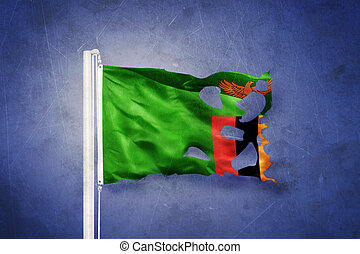 Torn flag of Zambia flying against grunge background.