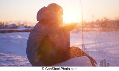 teen blows snow with hands on sunset background in closeup