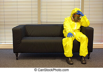 professional in protective clothing, mask and gloves,sitting and relaxing on the couch in office