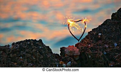 Heart shape sparkler burning on rocky coast in front of slow moving ocean water with orange warm sunset light on its surface, romance concept, romantic weekend in warm color.