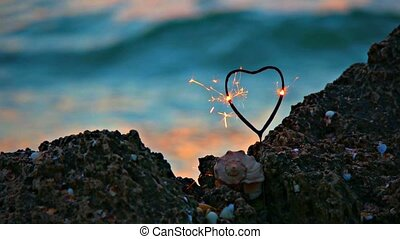Heart shaped sparkler burn on the rocky coast in front of slow moving sea water with orange warm sunset light on its surface, romance concept, romantic weekend