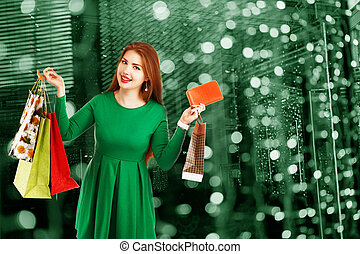 Beautiful happy girl posing with shopping bags against bokeh background