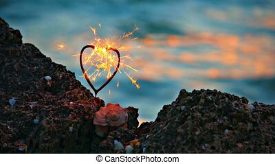 Heart-shaped sparkler and seashell on rocky sea shore, warm...