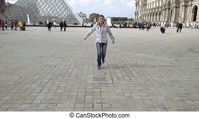 Woman jumps in Louvre palace courtyard - Smiling...