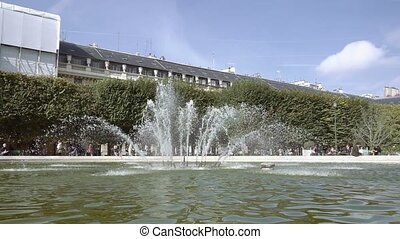 Running fountain surrounded by green trees and buildings on...