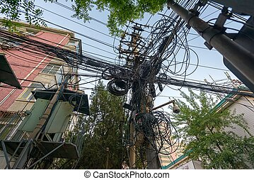 Large mount of power cables on wooden pylon in China
