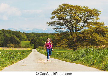 Kid girl running down the road in countryside on a very hot...