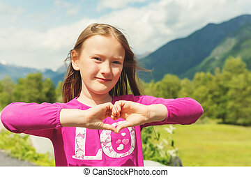 Outdoor portrait of a cute little girl making heart sign...