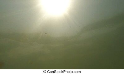 Sun in shallow water shining through wavy sea surface.
