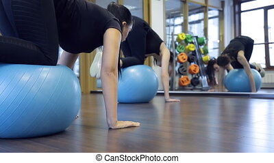 Woman athletes rock on gym ball press in fitness studio....
