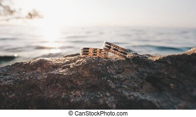 wedding rings on a stone - wedding rings lie on the sea rock
