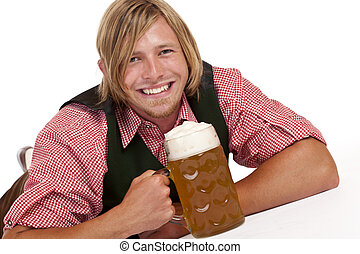 Happy man lying on floor holding oktoberfest beer stein...