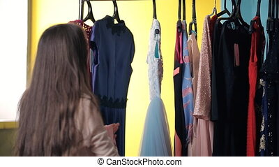 Young female is working in dressing room choosing dress....