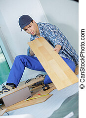 man laying parquet in clean room while sitting