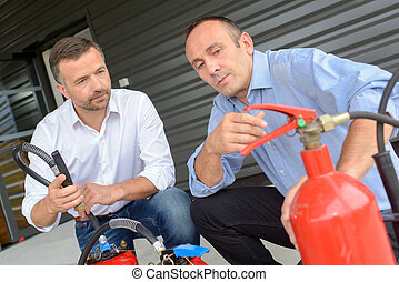 salesman explaining differences between fire extinguishers