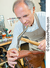 Cobbler using a hammer