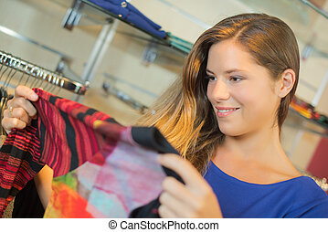 Lady holding modern top in clothes shop
